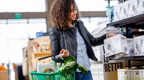 employee reading nutrition labels while grocery shopping